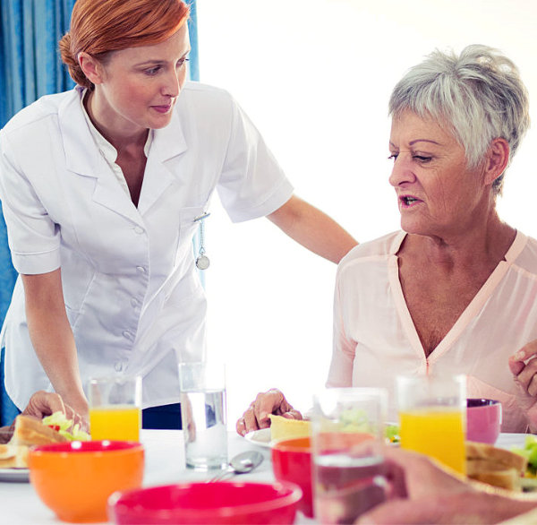 caretaker is preparing meals for her patients
