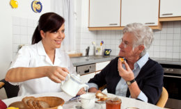 caretaker is preparing meal for her patient